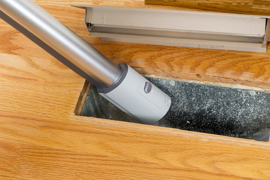 Horizontal photo of vacuum cleaning inside heater floor vent with Red Oak Floors in background. 7 Furnace Maintenance Tips.
