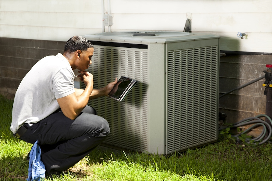 Home inspector, repairman, adjuster examines air conditioner units at a customer home. He is using his digital tablet to record results.